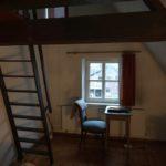 Der Schreibtisch im rechten Zimmer unterm Dach mit der Leiter zum